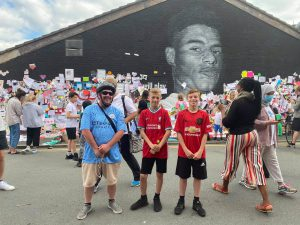 A Manchester City fan joins two young Liverpool and Manchester United supporters to stand together against racism at the defaced Marcus Rashford mural in Manchester